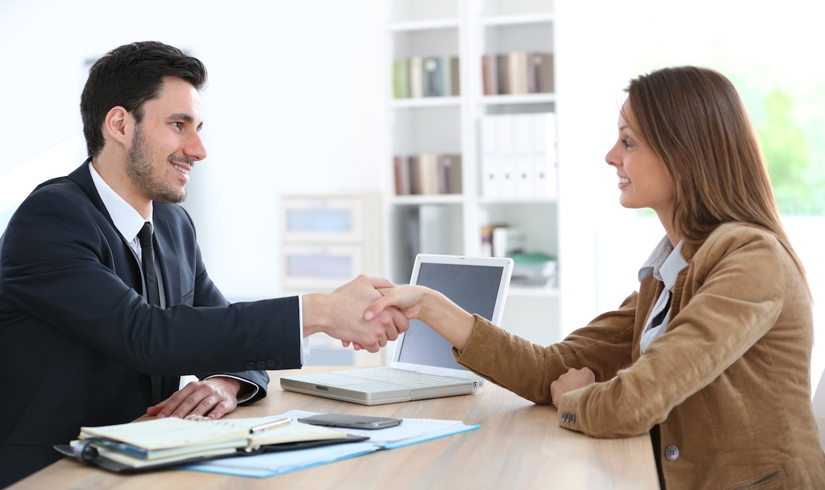 Woman giving handshake to financial adviser