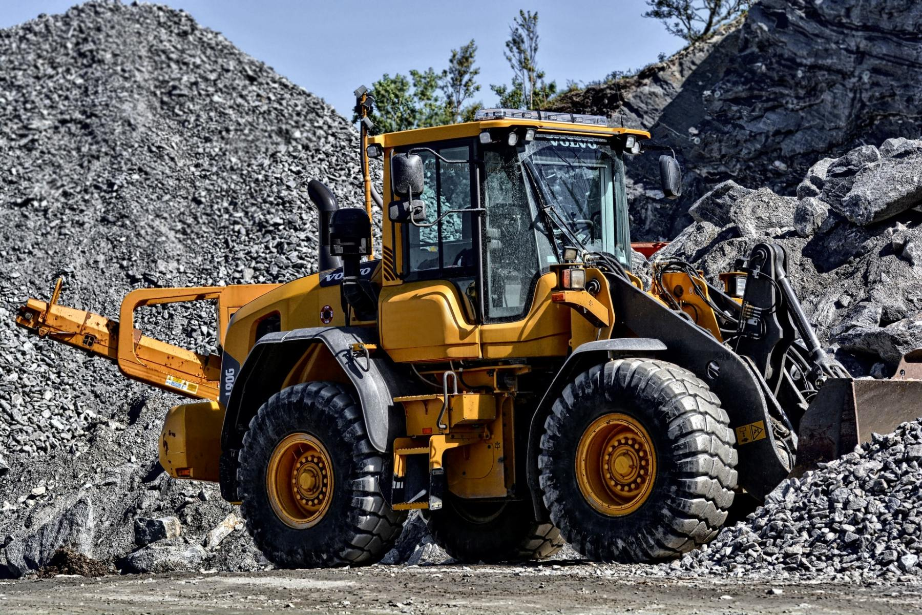 orange-and-black-tractor-next-to-piles-of-rocks-162639