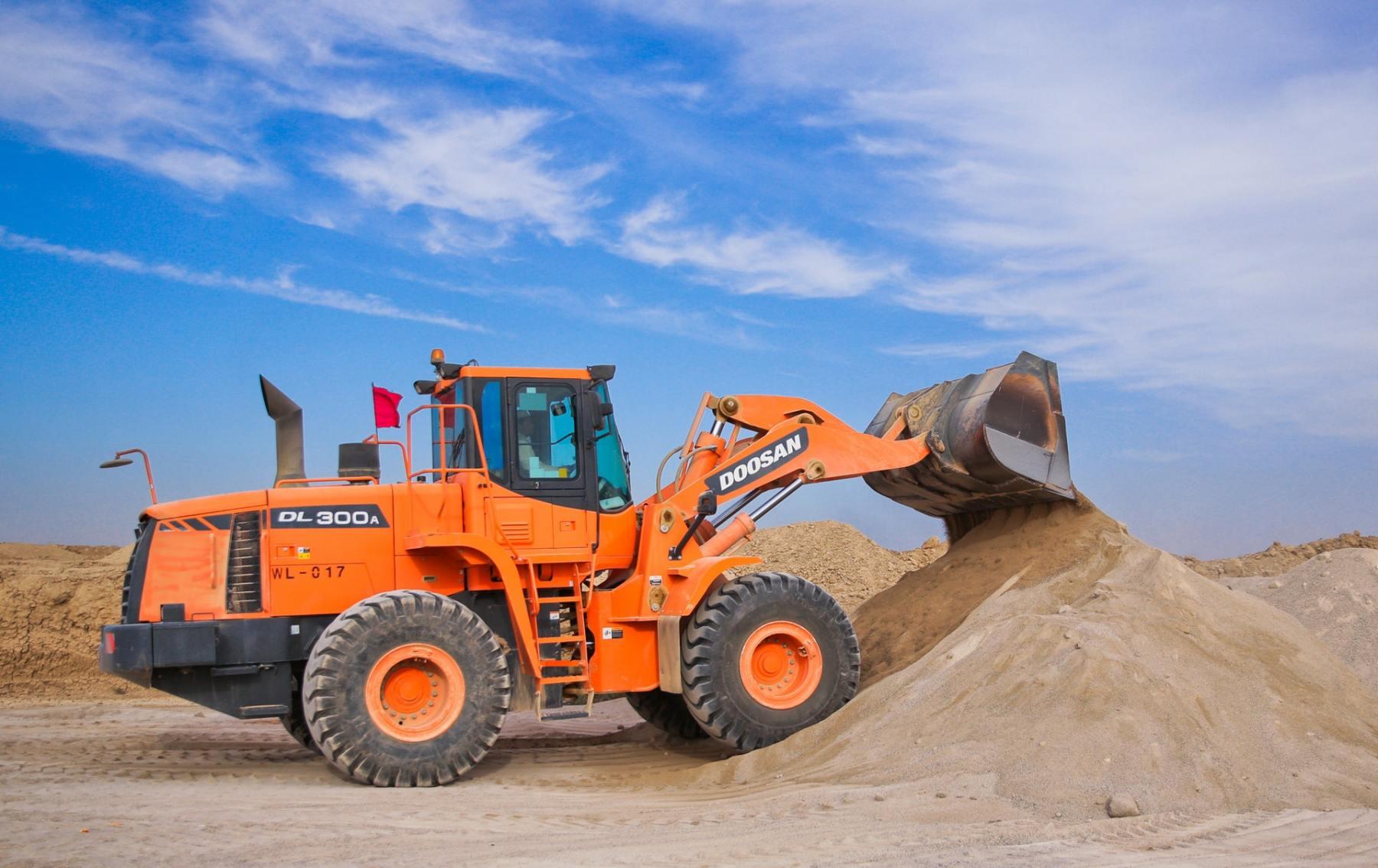 orange-excavator-on-brown-hill-1116035